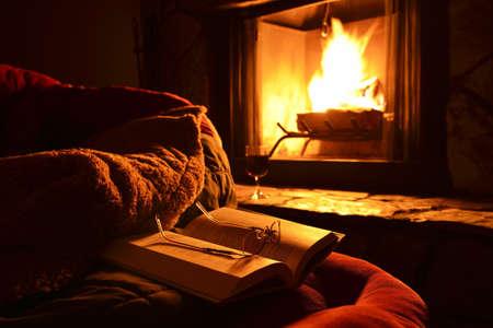 Entspannung mit einem Buch, Brille und einem Glas Wein vor dem Kamin in der Nacht