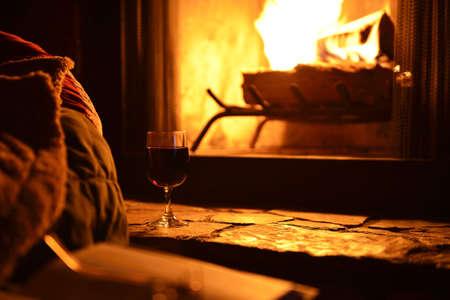 Entspannung mit einem Glas Wein vor dem Kamin in der Nacht Standard-Bild