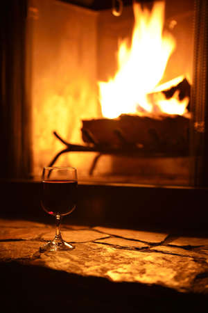 relaxation with a glass of wine in front of the fireplace at night photo