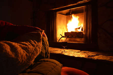 cosy: relaxation with a glass of wine in front of the fireplace at night