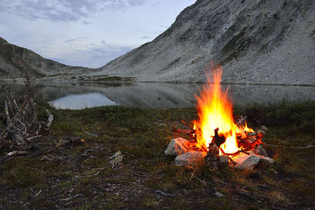 fire near the mountain lake at night in Medicine Bow Mountains, Wyoming during summer
