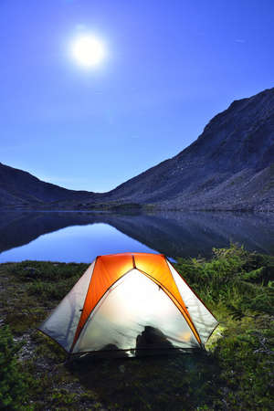tent on camping groud near the lake at night in moonlight during summer photo