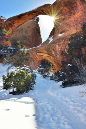 devils garden: Sun rays coming through the Double-O-Arch in Devils Garden in Arches National Park, Utah in winter, HDR