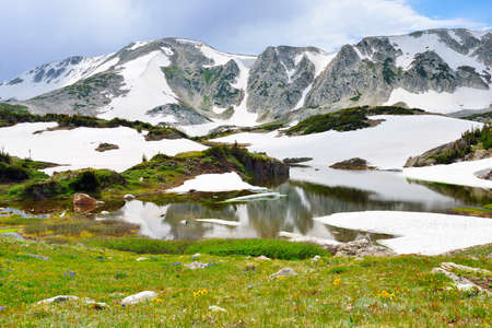 Snowy Range Mountains and apline lake with reflection in Medicine Bow, Wyoming in summer Stock Photo