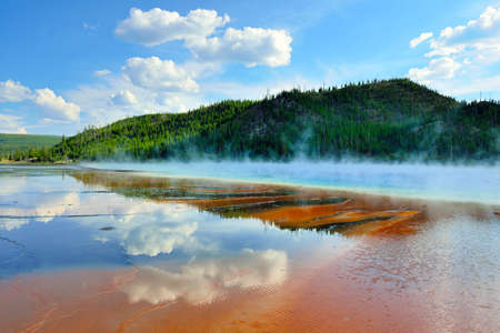 red steamy surface and reflection of the clouds in Midway Geyser Basin in Yellowstone National Park, Wyoming photo