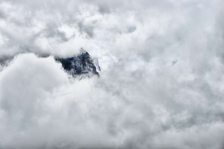 high and steep mountain surrounded by heavy clouds in Glacier National Park Stock Photo
