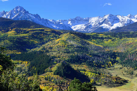 snow covered mountains: landscape view of the colorful alpine scenery with snow covered mountains during foliage season