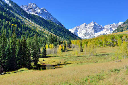 landscape view of the snow covered mountains with colorful yellow aspen during foliage season in Colorado Stock fotó