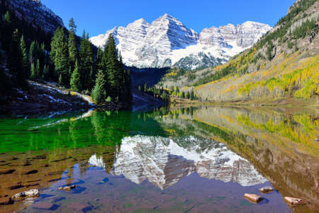 landscape view of the Maroon Bells during foliage season with snow covered mountains and yellow aspen reflecting in the lake, Colorado