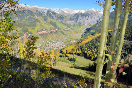 view of Telluride in the fall with yellow aspen and snow covered mountains