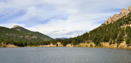 panoramic view of the mountains and alpine lake in bright daylight