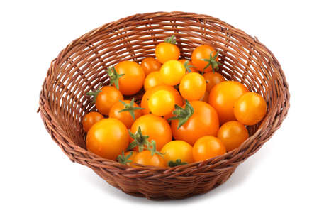 Yellow little tomatoes on wicked plate