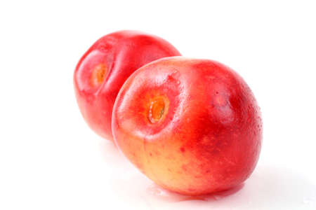 Two bicolor yellow-pink cherries isolated on white