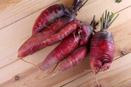 Red ugly carrots on table