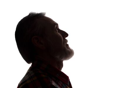 Portrait of a old man, unshaven, with beard, side view - dark isolated silhouette Stock Photo