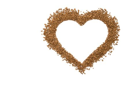 Dry instant coffee granules in the shape of a heart - brown texture, on a white background