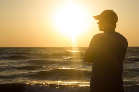 Portrait of a young man in cap on the beach - at sunrise
