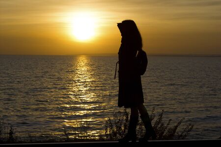 Girl walks on railroad tracks in a coat and boots on a sunset background - travel, depression, lifestyle