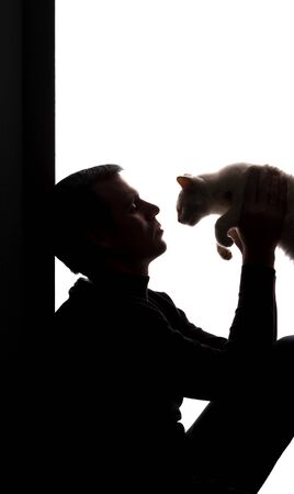 Young man with a kitten in his hands - silhouette