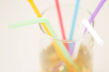 Multicolored tubes in a glass with a yellow drink - side view Foto de archivo - 150126952