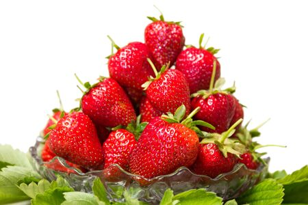 Ripe tasty strawberries with green leaves in a glass vase on a white background Zdjęcie Seryjne