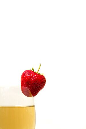 Red and ripe strawberry on the glass with a yellow drink, alcohol - half photo Zdjęcie Seryjne