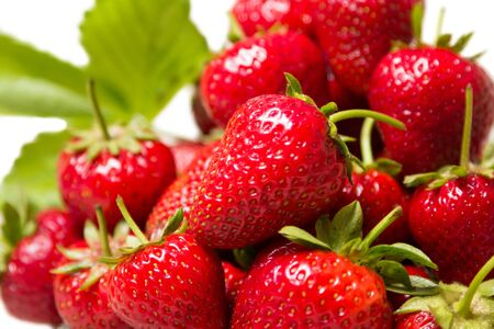Ripe tasty strawberries in a glass vase on a white background Imagens