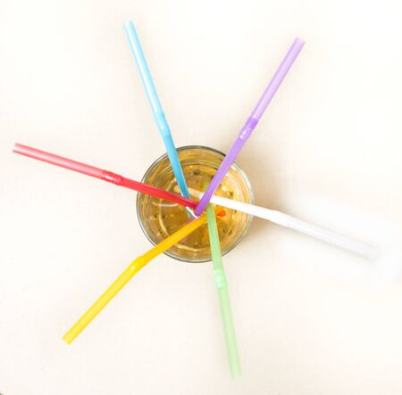 Multicolored tubes in a glass with a yellow drink - top view