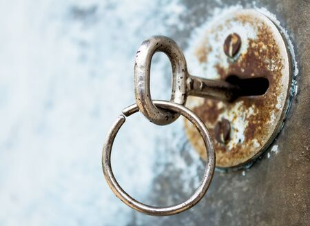 Old, rusty keyhole with key