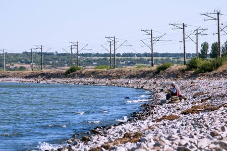 Fisherman on the beach in the summer of granite near the railroad