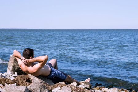 The young man relaxing sitting on a rock near the sea