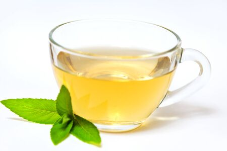 Glass transparent cup with tea and green mint leaf - on a white background