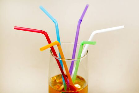 Multicolored tubes in a glass with a yellow drink - side view