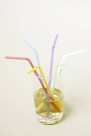 Multicolored tubes in a glass with a yellow drink - side view Foto de archivo - 150126846