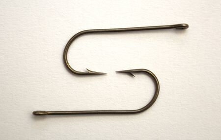 Two fishing hooks on a white paper background - closeup
