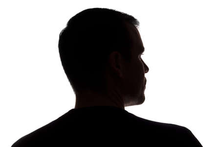 Portrait of a young man, unshaven, back view - dark isolated silhouette