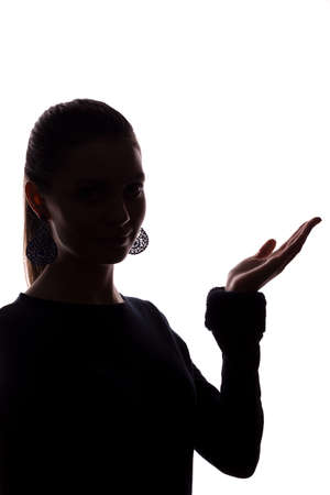 Young woman shows his index finger, hand forward - silhouette
