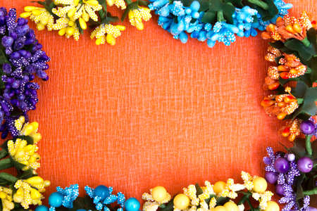 Frame of bright artificial flowers - multi-colored, beautiful background