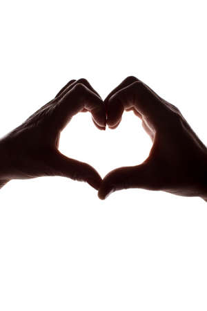 Female and male hands as a symbol of the heart - vertical silhouette