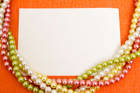Bright multi-colored beads with a blank sheet of paper - frame, beautiful background