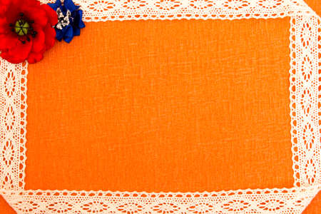 Sheet of paper, a fabric ribbon and bright artificial flowers - a multi-colored, beautiful background