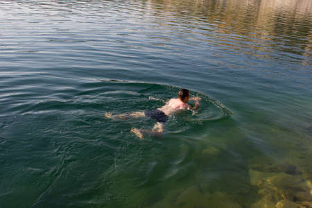 Male young swimmer on the water - background summer sunny sea