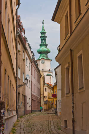 back alley: Narrow crooked cobbled bystreet with church tower in Bratislava Editorial