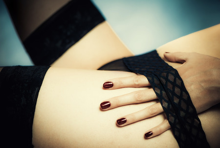 nude female: sexy female body part with fingers under panties stripe