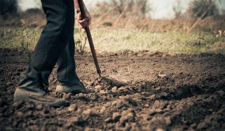 seeding: farmer working on a farmland at spring