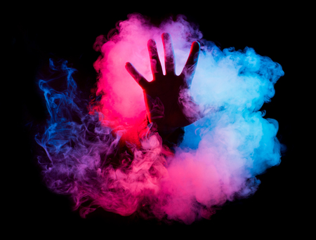 Hand reaching out from a colorful smoke on a black background