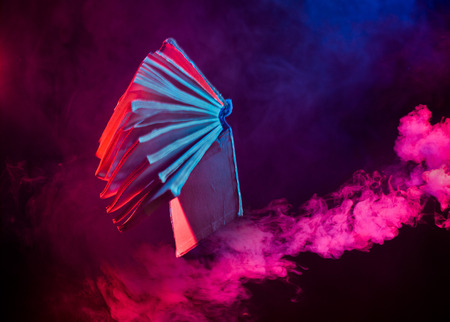 vintage book flying in colorful smoke on dark background