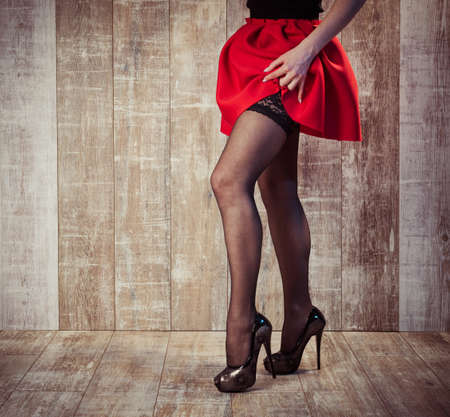 Young woman legs in black stockings and red skirt on wooden Banque d'images