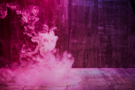 colorful red smoke isolated on a wooden background