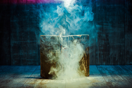 smoke from an open book on a wooden background